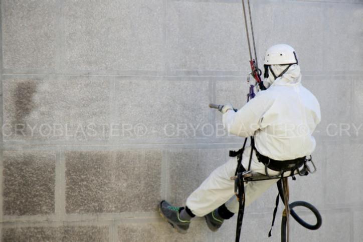 Opérateur effectuant un décapage de façade par aérogommage