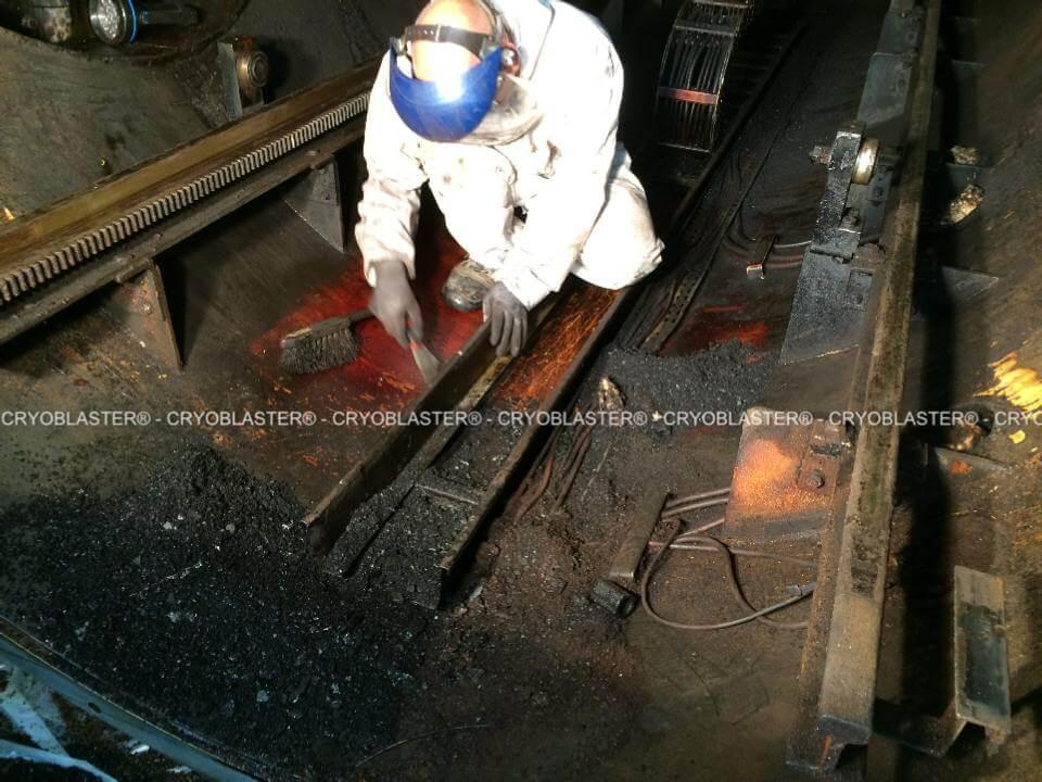 Personne utilisant une spatule pour une opération de décapage industriel sur tunnel