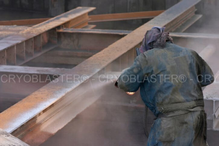 Homme décapant des poutres en acier par technique de sablage