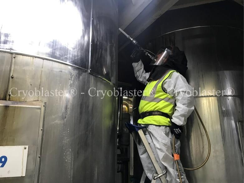 Opérateur de nettoyage cryogénique retirant de la colle sur une cuve inox